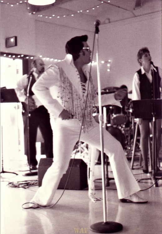 an Elvis impersonator, performing at a wedding reception