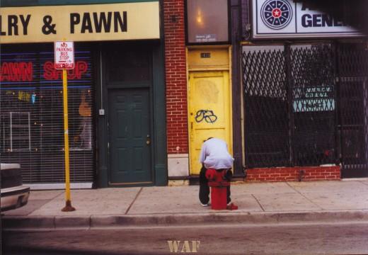 a Chicago street scene of a man sitting on a fire hydrant near a pawn shop