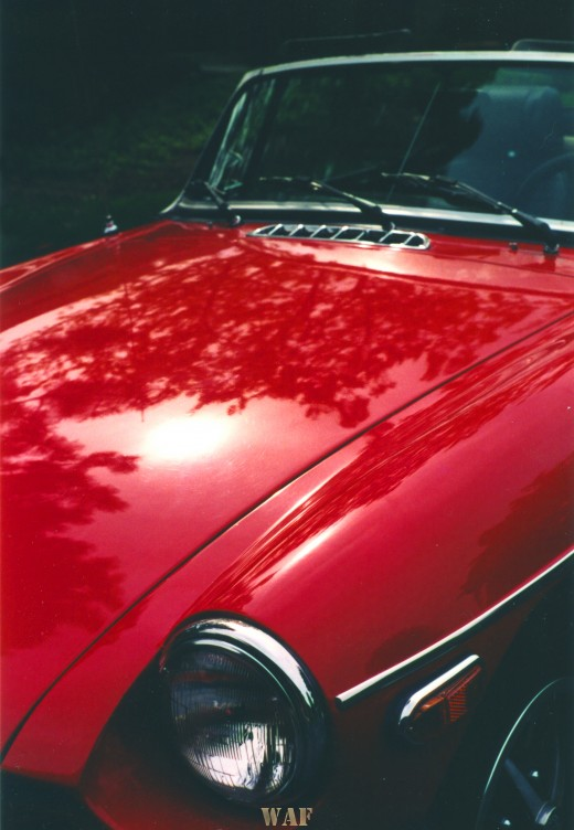 """a """"postcard corner"""" of the hood and front of a red MG Anniversary Edition convertible"""